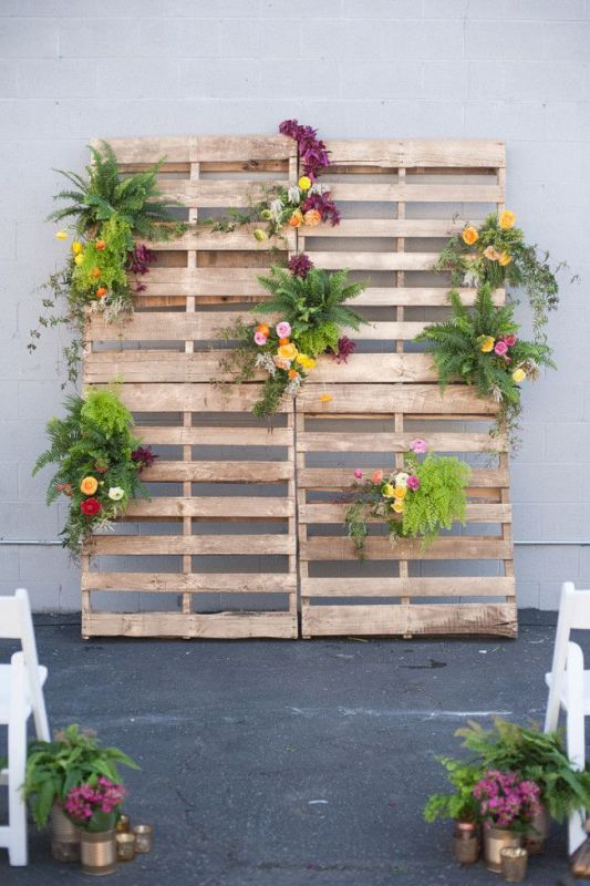 a wedding backdrop of pallets with greenery and bright blooms is a nice idea for the wedding ceremony or a photo booth