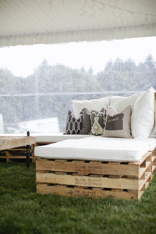pallet furniture with upholstery and pillows is a budget friendly and cool idea for your wedding lounge