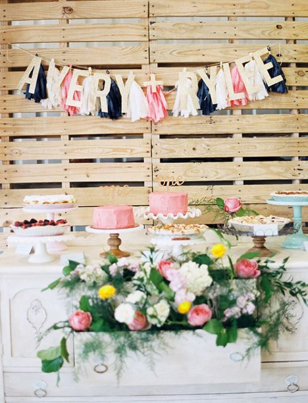 a pallet backdrop with colroful letters and tassel garlands can be used anywhere throughout your wedding venue
