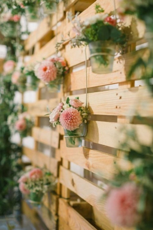 a pallet backdrop with sheer vases and greenery and pink floral arrangements can be used for ceremonies, cake tables, photo booths and so on