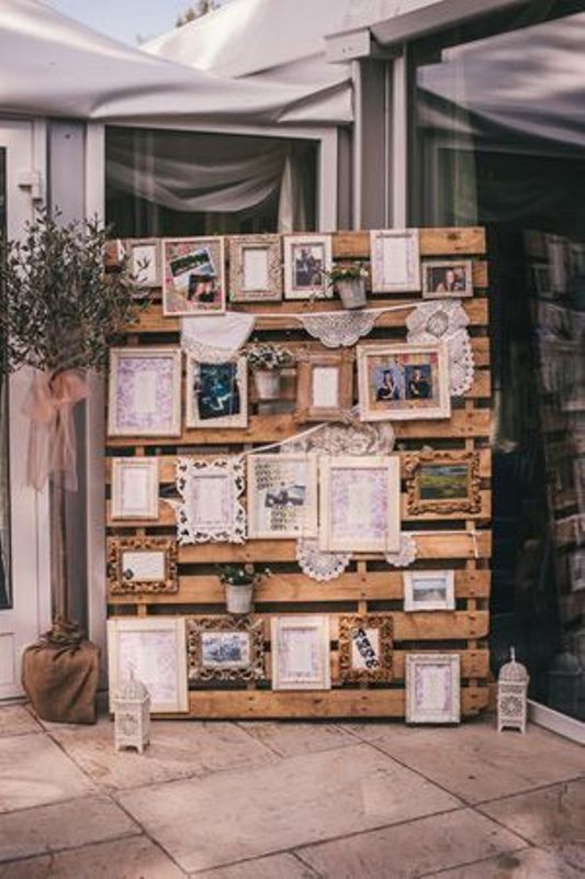 a pallet wedding backdrop with a gallery wall of photos, paintings and other meaningful stuff and lanterns