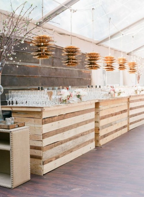 a large wedding drink station fully built of pallet wood is a cool recycling idea for a rustic wedding