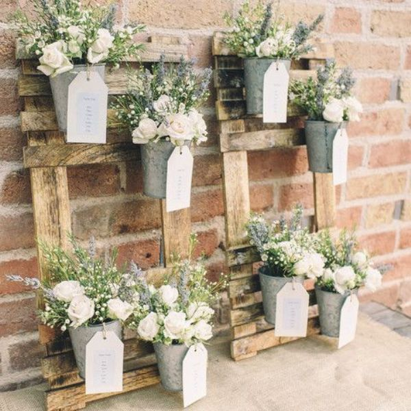 pallet vertical gardens with buckets, fresh blooms and greenery plus tags for a rustic wedding