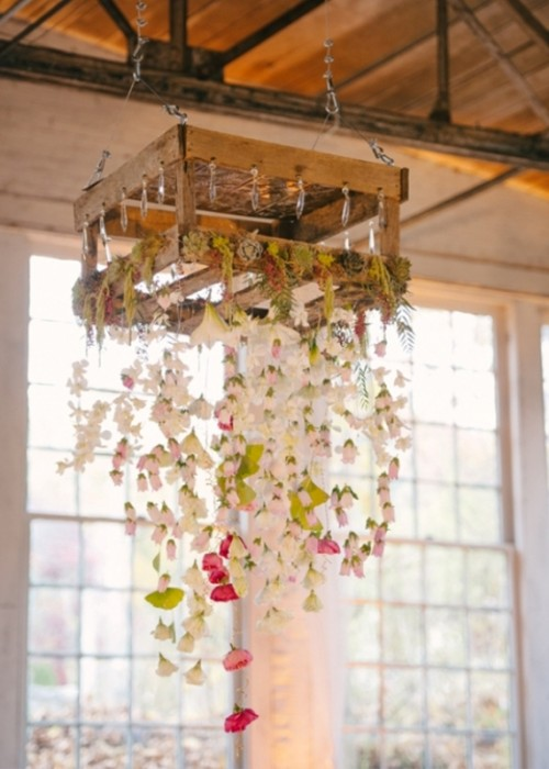 a pallet with flower garlands hanging down and some succulents and moss on top is a simple and cute alternative to an overhead installation