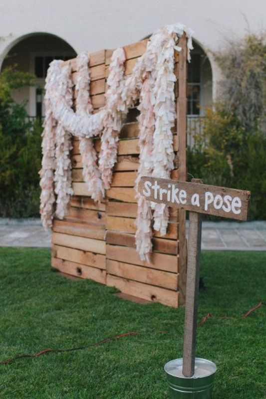 a photo booth backdrop made of pallets with blush and white paper garlands is an easy and eco friendly idea