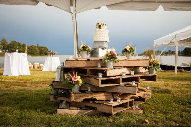 a dessert table fully made of pallets with candles, floral arrangements and a wedding cake on top