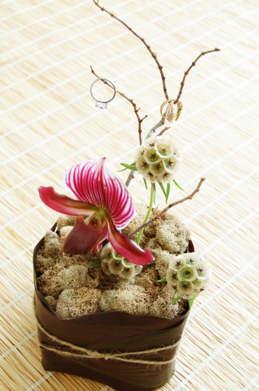 an arrangement of moss, blooms and twigs with wedding rings on top is great for an exotic wedding