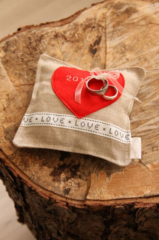 a burlap pillow with a heart applique on top is a pretty pillow idea for a rustic wedding