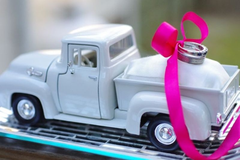 a vintage toy pickup with rings attached with a bright pink ribbon box is a fun idea for a retro infused wedding