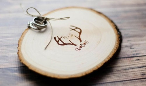 a burnt wood slice with antlers and twine is a cool idea for a rustic or woodland wedding