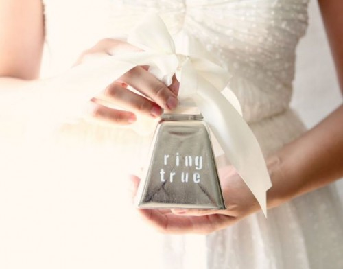 a tin box with a large creamy bow on top is a whimsical idea for carrying wedding rings