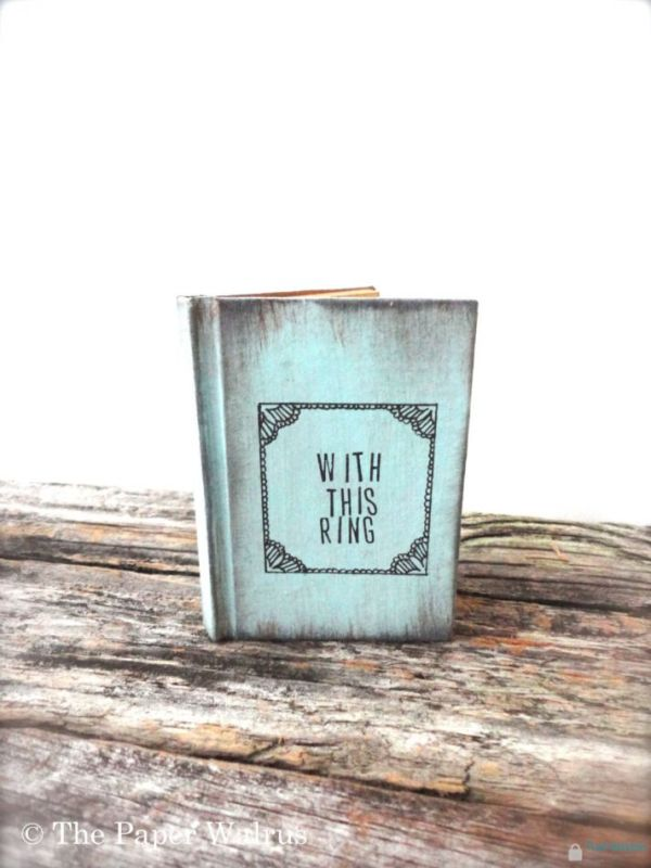 a blue vintage book with wedding rings inside is a fun idea for a book loving wedding