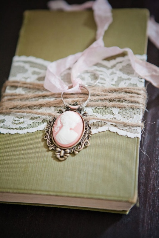a green book with lace and twine plus a vintage necklace on top is a cool idea to attach your rings