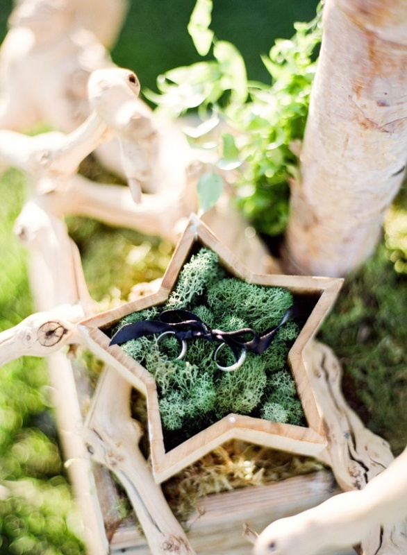 a wooden star filled with moss and with rings is a creative idea for a woodland wedding
