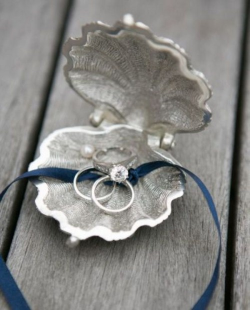 a metal seashell with a blue ribbon is a cool idea for a coastal or a beach wedding