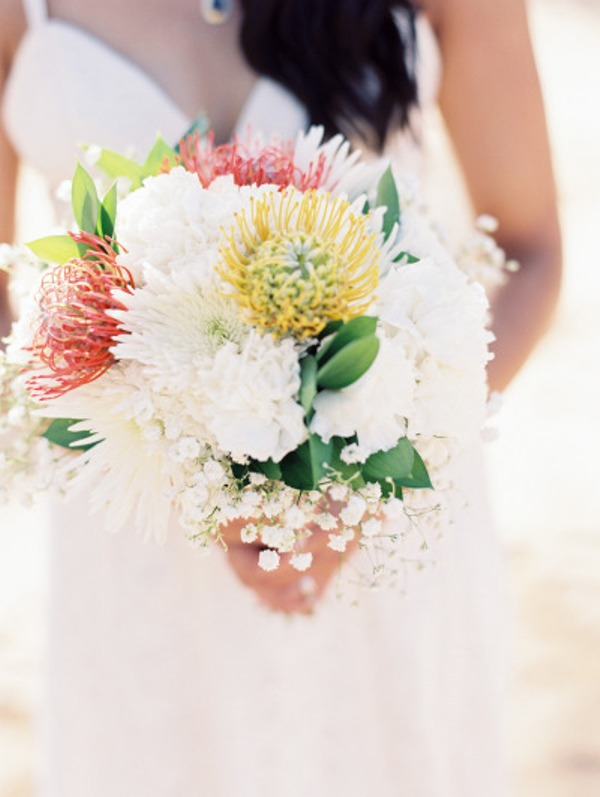 a lovely beach wedding bouquet of white blooms and red and yellow pincushion proteas, baby's breath and leaves