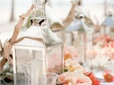 a bold beach wedding tablescape with driftwood, candles, bright blooms, air plants and glasses