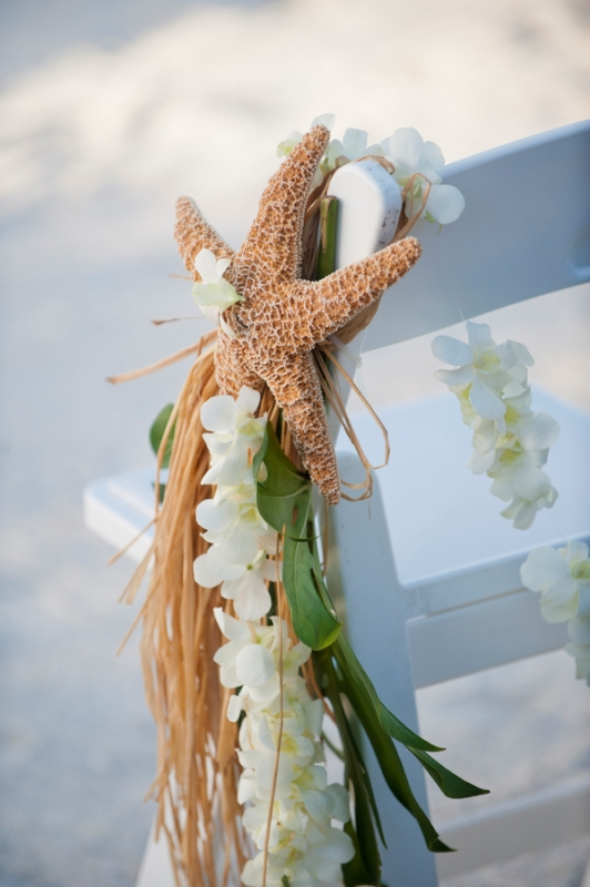 accent wedding chairs with white orchids, greenery and a starfish to make them look tropical and beach like