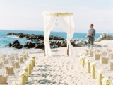 a chic beach wedding ceremony space with acrylic chairs, white blooms in tall vases and a breezy wedding arch decorated with fabric