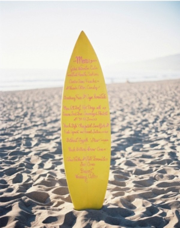 a bright yellow surf board as a beach wedding menu is a fun and beach infused idea for your decor