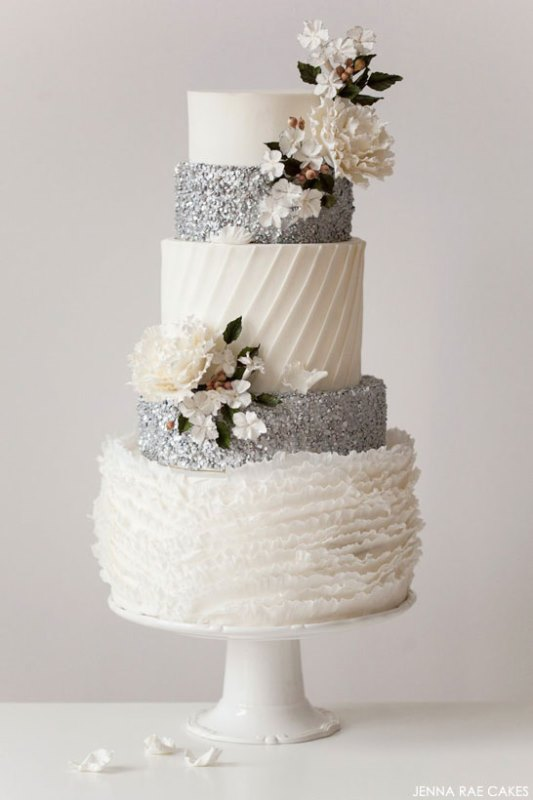 a white and silver wedding cake with silver glitter and patterned tiers and some sugar blooms is a beautiful dessert