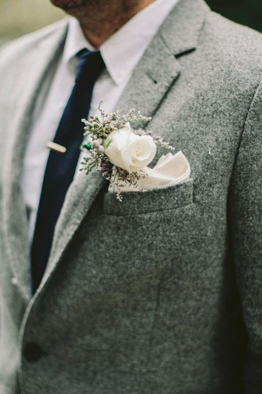 a grey woolen jacket with a black tie and a white flower boutonniere for a stylish and casual groom's look
