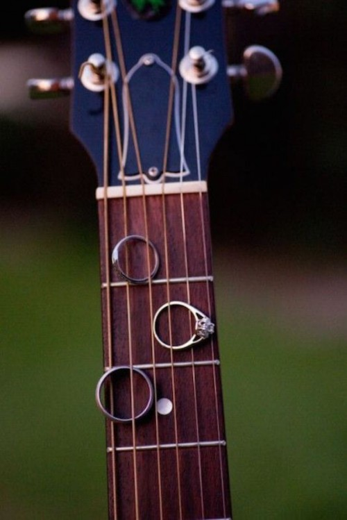 wedding rings displayed on a guitar fingerboard to show off the love of the couple to music