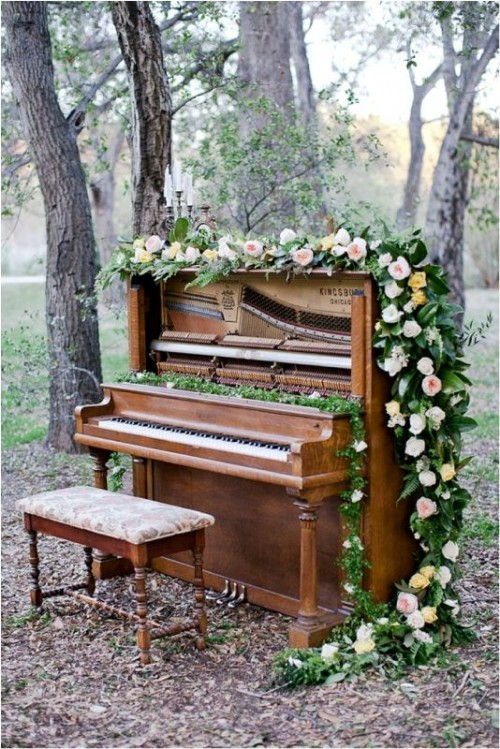a beautiful piano decorated with lush greenery and blush blooms can be used to gift a song to each other, for the ceremony and to take pics