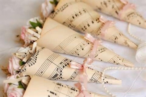 cones of note paper with pink blooms can be used throughout the venue to decorate it in various ways