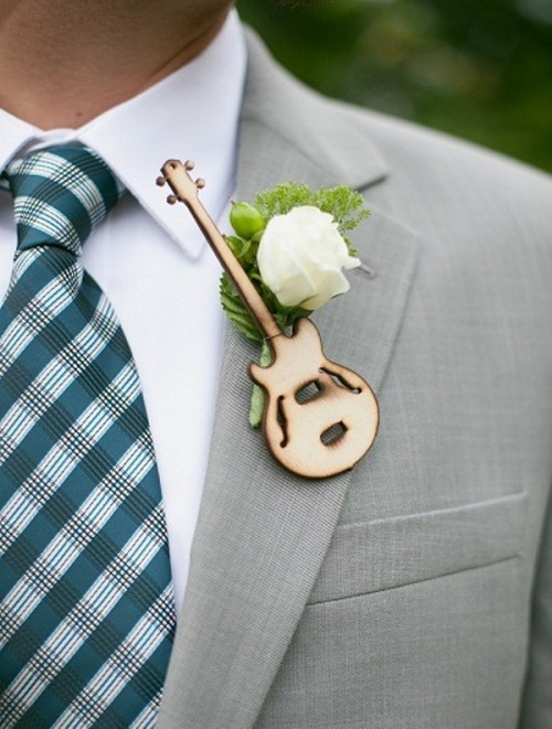 a fun boutonniere with a burnt out guitar and a single white bloom for accessorizing the groom's suit