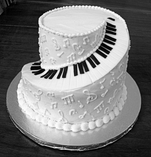 a black and white wedding cake showing off piano key buttons and notes on its sides