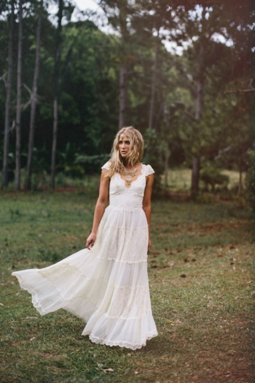 a lace A-line boho elopement wedding dress with cap sleeves, a deep V-neckline and layered necklaces