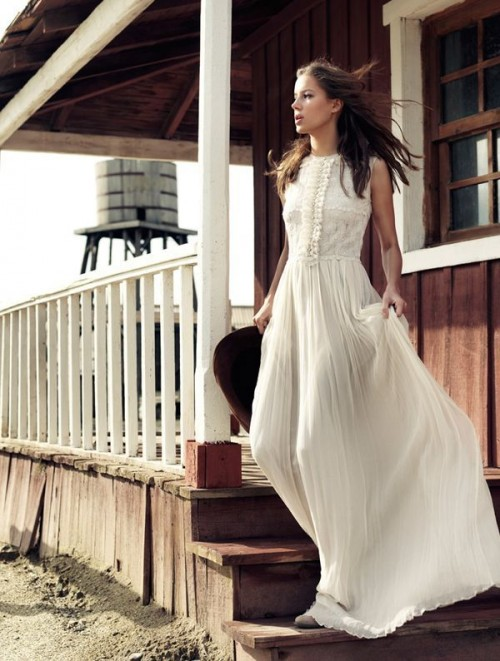 a vintage-inspired wedding dress with a sleeveless lace bodice, a pleated maxi skirt, booties and a cowboy hat for a vintage elopement