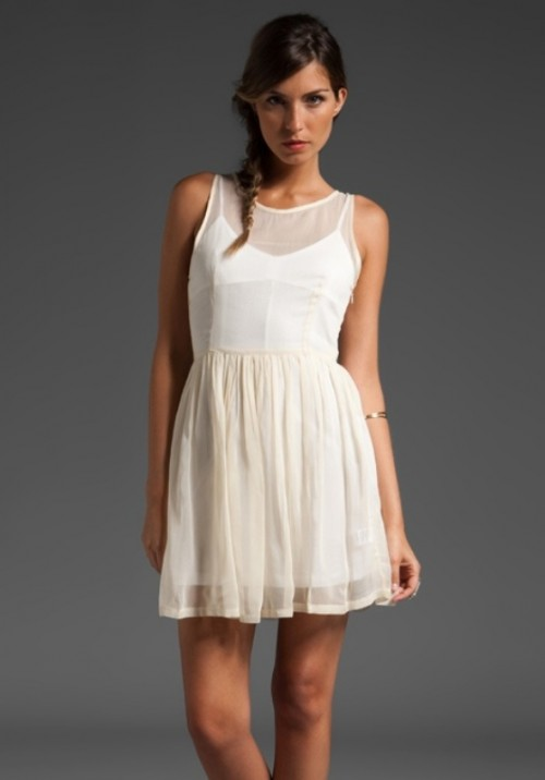 a modern white mini dress with no sleeves and an illusion neckline, with a pleated skirt is ideal for a city hall elopement