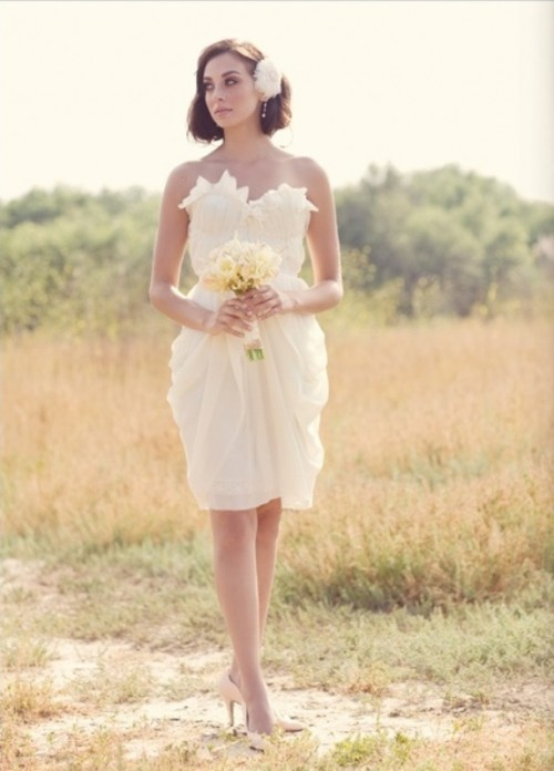 a whimsical white structured wedding dress with a floral applique strapless neckline and a draped skirt plus a floral headpiece