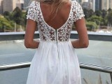 a white mini dress with a floral bodice with a cutout back and short sleeves and a pleated skirt