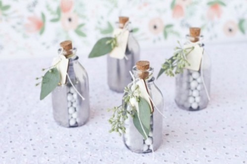 mercury glass bottles with candies and soem fresh greenery attached to them