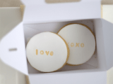 a box with two glazed cookies with LOVE and XOXO are a cool modern idea for a rehearsal dinner