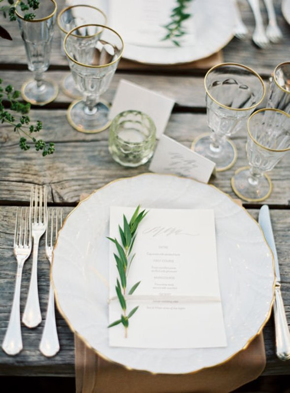 have amazing non covered weathered wood tables decorated with greenery and accented with gilded edge glasses, plates and gold cutlery