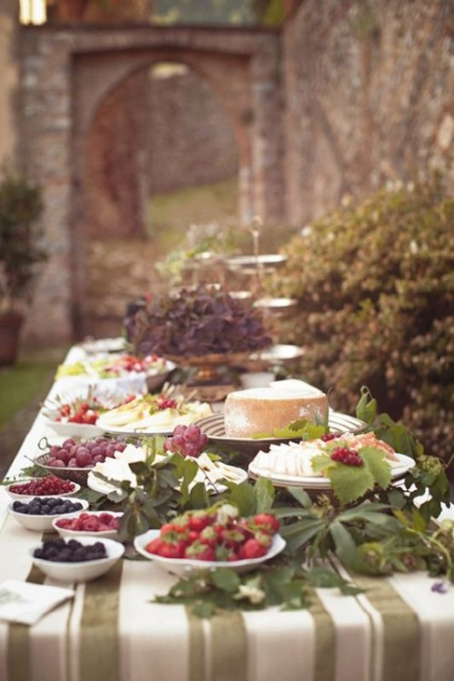 a fantastic cheese and grapes food bar decorated with greenery is a cool food station idea for a Tuscany wedding