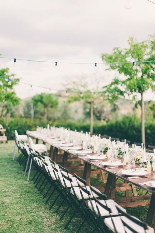 an uncovered table with greenery, lemons and candles for a chic yet relaxed Tuscany wedding