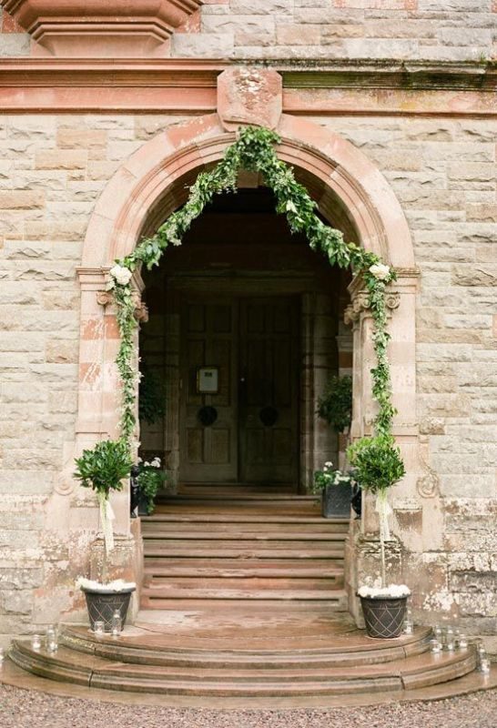decorate the entrance with greenery garlands and potted greenery and put candles on the steps