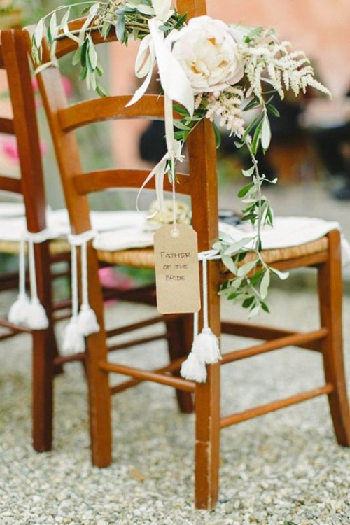 decorate wedding chairs with greenery, tags and tassels and some lovely neutral blooms to make them look cool