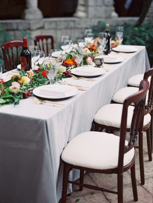 a gorgeous Italian wedding tablescape with greenery, bold blooms and grapes as a table runner is amazing