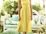 a yellow midi dress with pleating, with a sash and thick straps forming a halter neckline is a vintage-inspired wedding guest outfit idea