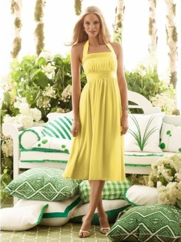 a yellow midi dress with pleating, with a sash and thick straps forming a halter neckline is a vintage inspired wedding guest outfit idea