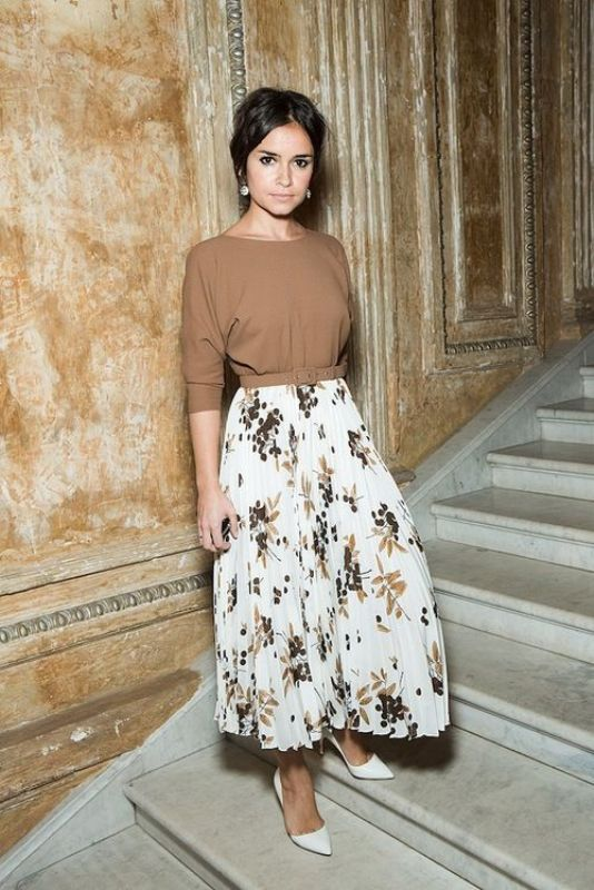 a fall wedding guest outfit with a beige top with short sleeves and a high neckline and a pleated midi with floral prints in the same color, white heels and statement earrings
