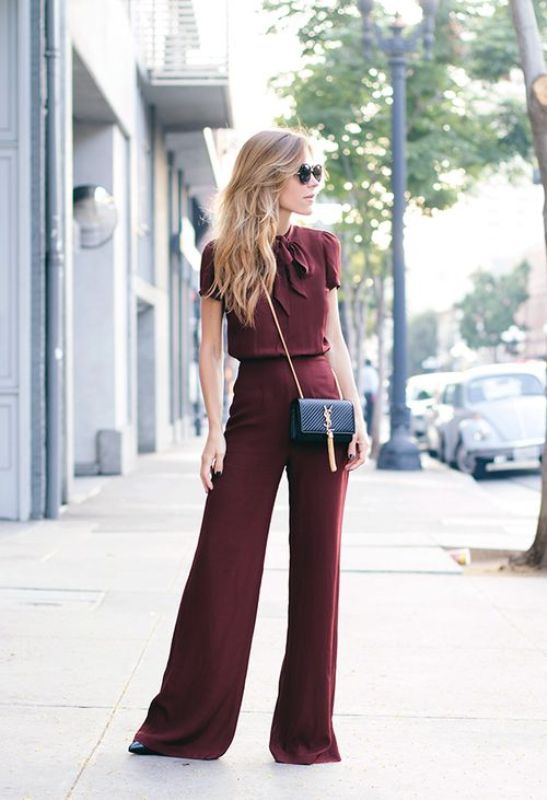 a burgundy jumpsuit with a fitting bodice and palazzo pants, a black mini bag and black heels for a fall or winter wedding