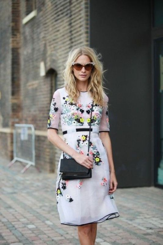 a white dress with black touches and bold floral embroidery styled wiht a black bag and shoes for a bold and chic spring or summer wedding guest look