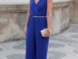an electric blue jumpsuit with a V-neckline and palazzo pants, with a polished belt, a neckline and a mini clutch for a formal wedding guest look